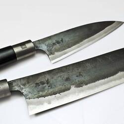 """La serie CHROMA Haiku Kurouchi fa parte della prestigiosa gamma TAKUMI di CHROMA Knife. Realizzati  esclusivamente dal maestro artigiano Takumi, Kurouchi tradotto dal giapponese significa """"forgiato in nero"""". Ed è per la sua maestria artigianale e la natura unica, che viene chiamato orgogliosamente """"il coltello originale"""". Il coltello Kurouchi deve il tipico carattere arcaico alle sue origini: la regione di Tosa nel sud del Giappone. Oltre alla lunga tradizione nella fabbricazione di coltelli, la regione di Tosa è conosciuta per il suo paesaggio aspro e selvaggio, caratteristiche che si riflettono nelle lame Kurouchi conferendo a questo coltello un'immagine e una personalità inconfondibili. Dopo essere stato forgiato, il CHROMA HAIKU Kurouchi viene lavorato in modo che la lama rimanga di un nero opaco e solo il tagliente estremamente affilato risalti con un bagliore metallico.  La lama prevede una """"costruzione a sandwich"""" composta da acciaio AOKO blu( acciaio al carbonio) estremamente duro al centro, e poi rifinita con strati protettivi di acciaio consecutivamente più morbido per una maggiore flessibilità e stabilità. Un dettaglio particolare e suggestivo del manico del CHROMA HAIKU Kurouchi è il bolster in acciaio inossidabile, con il perno Mekugi, anch'esso in acciaio inossidabile, tipico della linea Haiku. Il manico, in accordo con la lama, è realizzato in legno massello di magnolia nero satinato. Scopri la serie sul nostro shop online  https://bit.ly/3nFkbTq"""